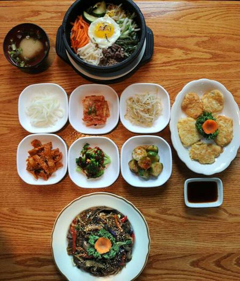 A typical dinner for two at Seoul Restaurant, New Haven. Entrees Stone Pot Bibim Bap top, Chapchae bottom, and a codfish appetizer, right, all around Pan Chan side dishes.  Mara Lavitt/New Haven Register10/2/12