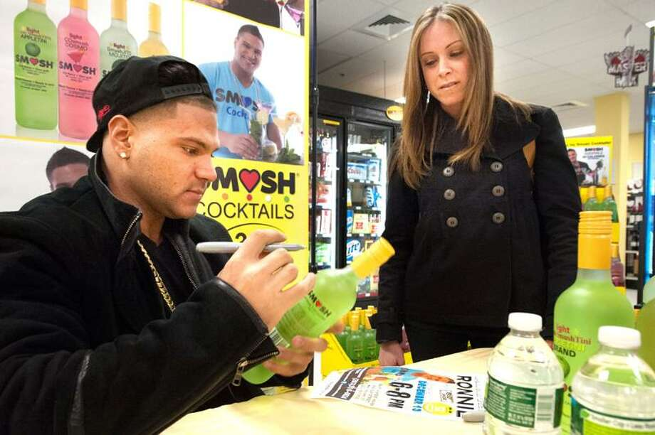"""Ronnie Magro of MTV's Jersey Shore signs a bottle of of his 34-calorie """"Smush"""" Cocktail for Lacey D'Amato of East Haven at Bevmax Liquor Store 480 Elm Street in West Haven December 13, 2012. vm Williams"""