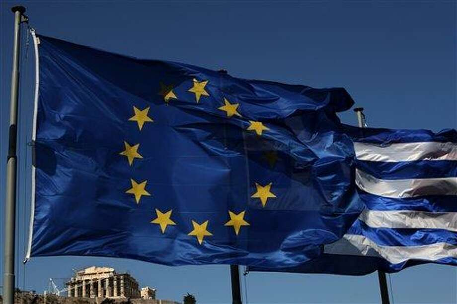 An EU and a Greek flag fly in front of ancient Parthenon temple Sunday in Athens as Greeks vote in the most crucial elections in decades. Greece voted amid global fears that victory by parties that have vowed to cancel the country's international bailout agreements and accompanying austerity measures could undermine the European Union's joint currency and pitch the world's major economies into another sharp downturn. Associated Press Photo: AP / AP