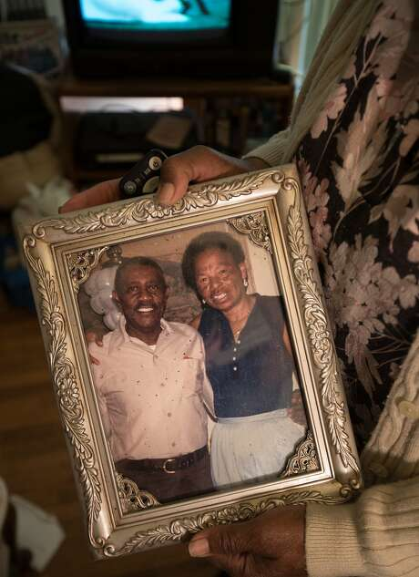 Dorothy DeBose holds a photo of her late father and stepmother, Ernest and Bessie DeBose, who owned the foreclosed home. Photo: Paul Kuroda, Special To The Chronicle
