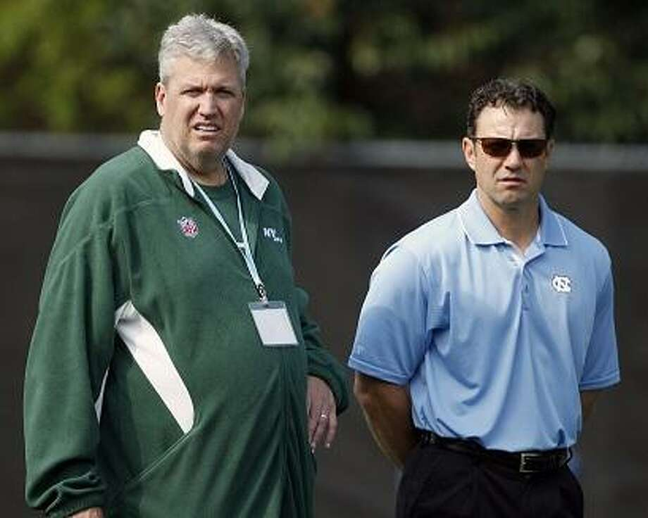 New York Jets head coach Rex Ryan, left, stands with new North Carolina head coach Larry Fedora and watches the Tar Heel football players perform during North Carolina's pro NFL football day in Chapel Hill, N.C., Tuesday, March 20, 2012. (AP Photo/Bob Leverone) Photo: ASSOCIATED PRESS / AP2012