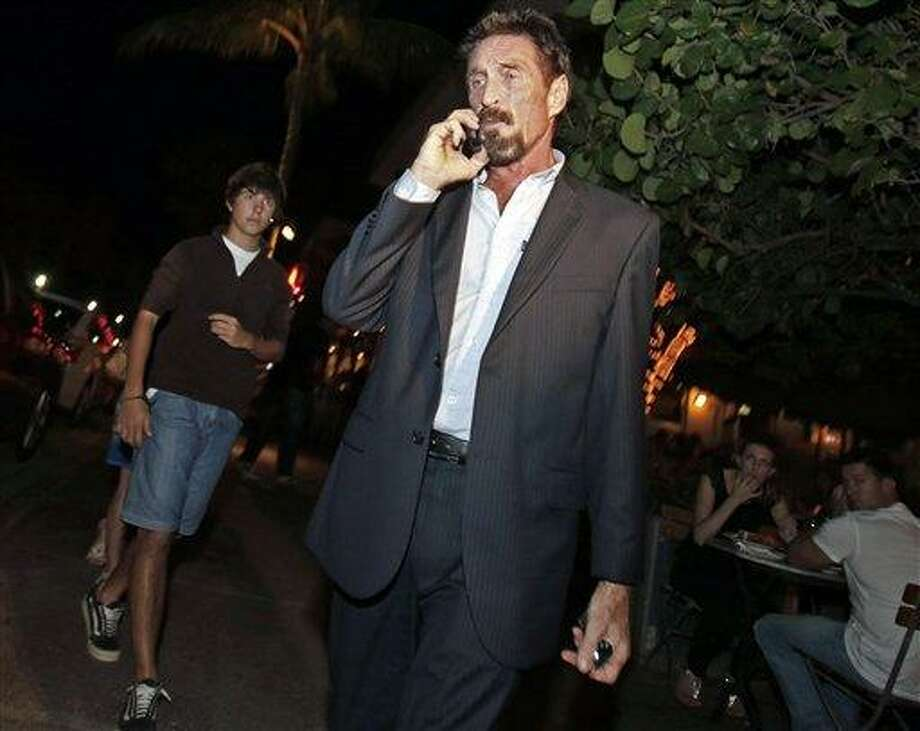 Anti-virus software founder John McAfee talks on his mobile phone as he walks on Ocean Drive in the South Beach area of Miami Beach, Fla., on his way to dinner Wednesday, Dec 12, 2012. McAfee arrived in the U.S. on Wednesday night after being deported from Guatemala, where he had sought refuge to evade police questioning in the killing of a man in neighboring Belize.(AP Photo/Alan Diaz) Photo: AP / AP