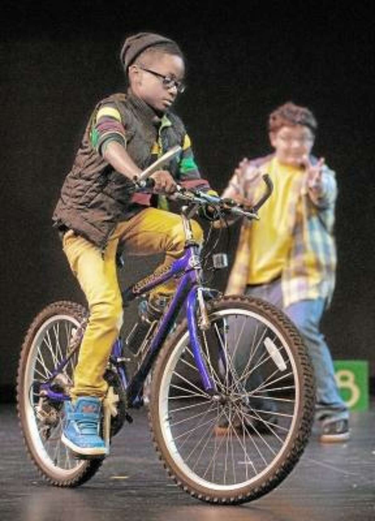 """Catherine Avalone/The Middletown Press Owen, played by Mark Sumner, 15, right, teaches young Q Phipps played by D'Andrew Saunders, 10, to ride a bike during rehearsal Monday night of """"Bigger Than You Think,"""" a collaborative effort by the Middletown Youth Services Bureau, The Center for the Advancement of Youth, Family and Community Services and Community Performance International. Written by award-winning playwright Jules Corriere and directed by Richard Geer, the one-act play is based on several childhood stories of residents and will be performed by a cast of 40 tonight at 7, followed by an open community conversation at 8 at the Middletown High School Performing Arts Center."""