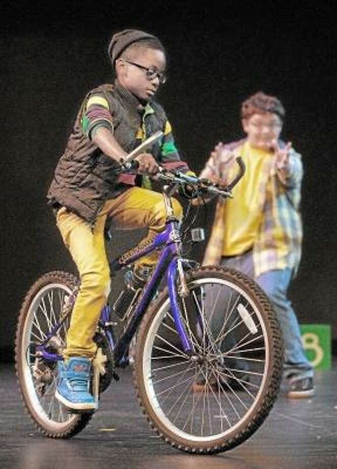 "Catherine Avalone/The Middletown Press  Owen, played by Mark Sumner, 15, right, teaches young Q Phipps played by D'Andrew Saunders, 10, to ride a bike during rehearsal Monday night of ""Bigger Than You Think,"" a collaborative effort by the Middletown Youth Services Bureau, The Center for the Advancement of Youth, Family and Community Services and Community Performance International. Written by award-winning playwright Jules Corriere and directed by Richard Geer, the one-act play is based on several childhood stories of residents and will be performed by a cast of 40 tonight at 7, followed by an open community conversation at 8 at the Middletown High School Performing Arts Center."