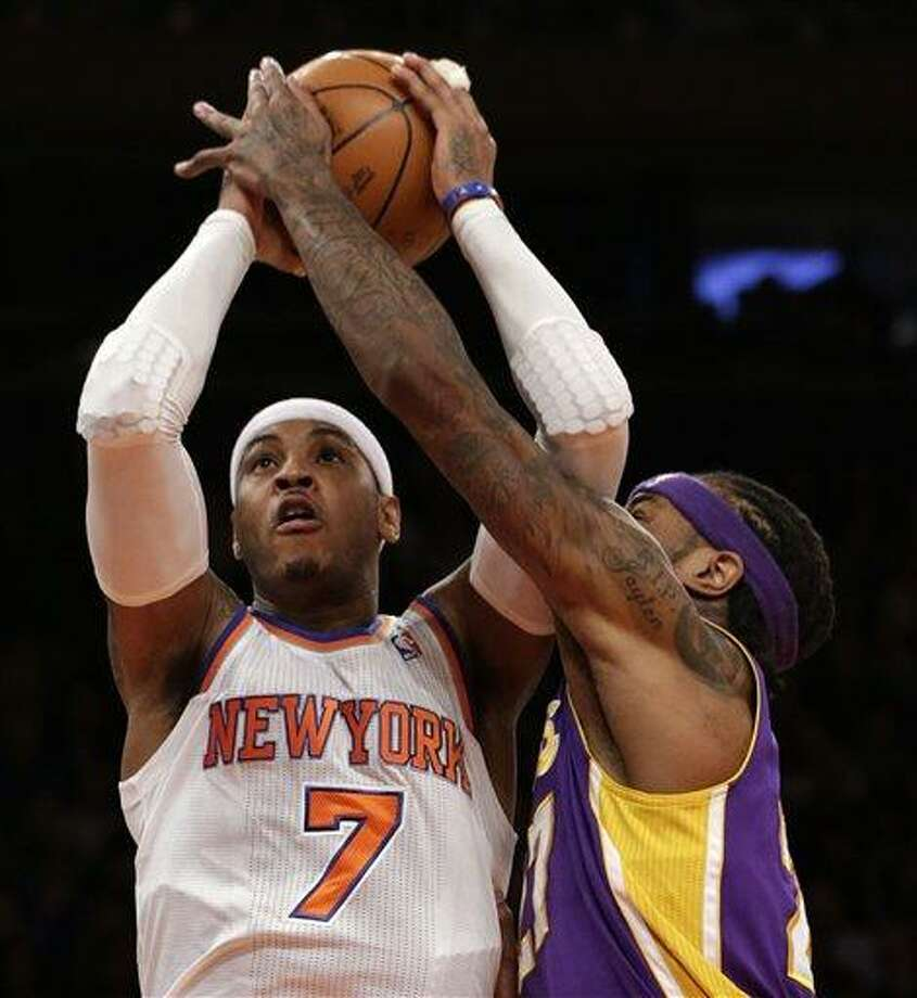 Los Angeles Lakers center Jordan Hill,right, gets his hand on the ball as New York Knicks forward Carmelo Anthony, left, goes up for a layup in the first half of their NBA basketball game at Madison Square Garden in New York, Thursday, Dec. 13, 2012.  (AP Photo/Kathy Willens) Photo: ASSOCIATED PRESS / AP2012