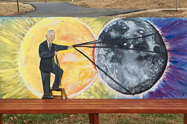 A bench outside the recreation department in Hopkinsville, Ky. depicts two town highlights: the coming solar eclipse, with Hopkinsville-born mystic Edgar Cayce lassoing the moon.