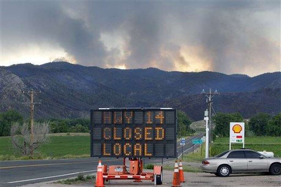 A sign warns motorist of the closure of Highway 14 through Poudre Canyon as columns of smoke rise in the distance from the High Park wildfire west of Fort Collins, Colo., on Friday,  June 15, 2012. The wildfire started Saturday and has burned over 50,000 acres. (AP Photo/Ed Andrieski) Photo: AP / AP