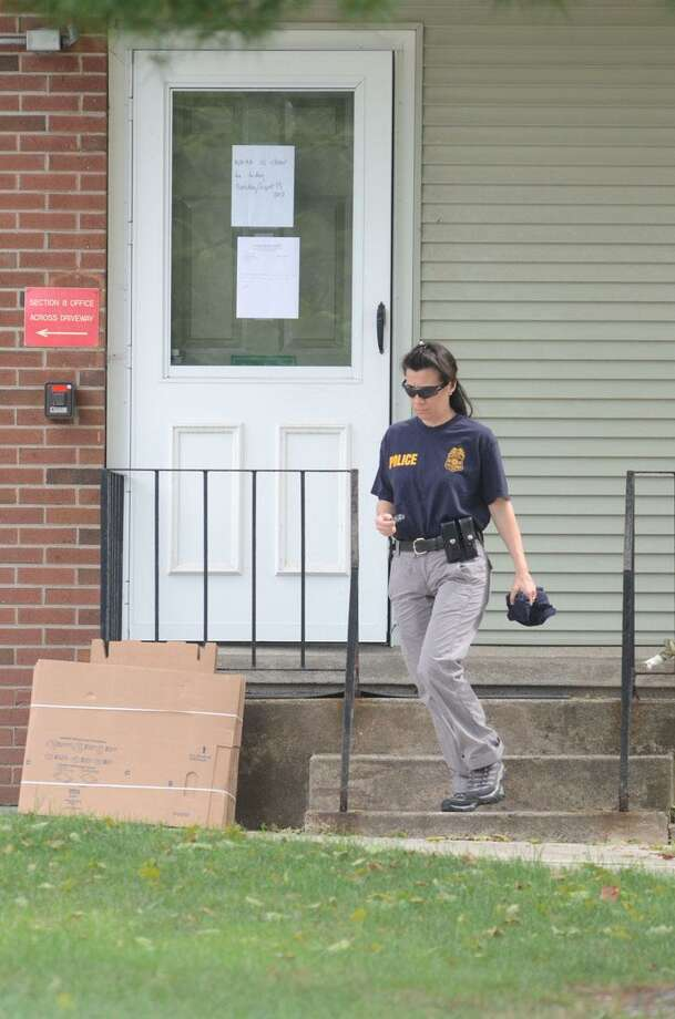 Police exit the West Haven Housing Authority building Tuesday. VM Williams/Register