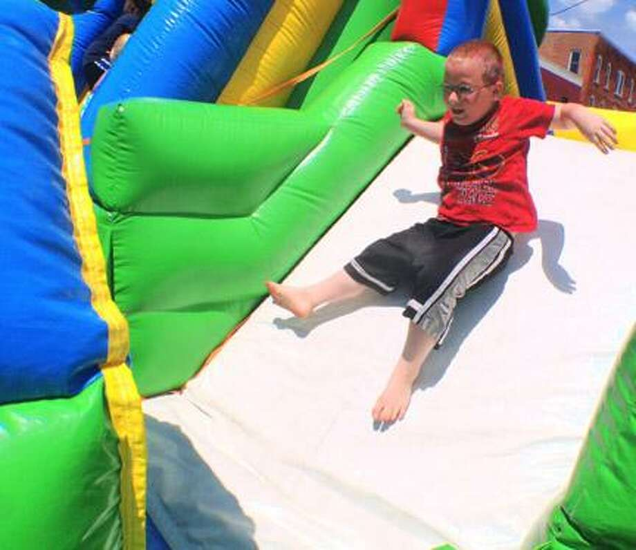 "Dispatch Staff Photo by JOHN HAEGER <a href=""http://twitter.com/oneidaphoto"">twitter.com/oneidaphoto</a> Dokata Lighthaul 6, of Oneida slides down one of the bounce houses during the annual Rock the Block held by Church on the Rock on Saturday, June 16 , 2012 in Oneida."