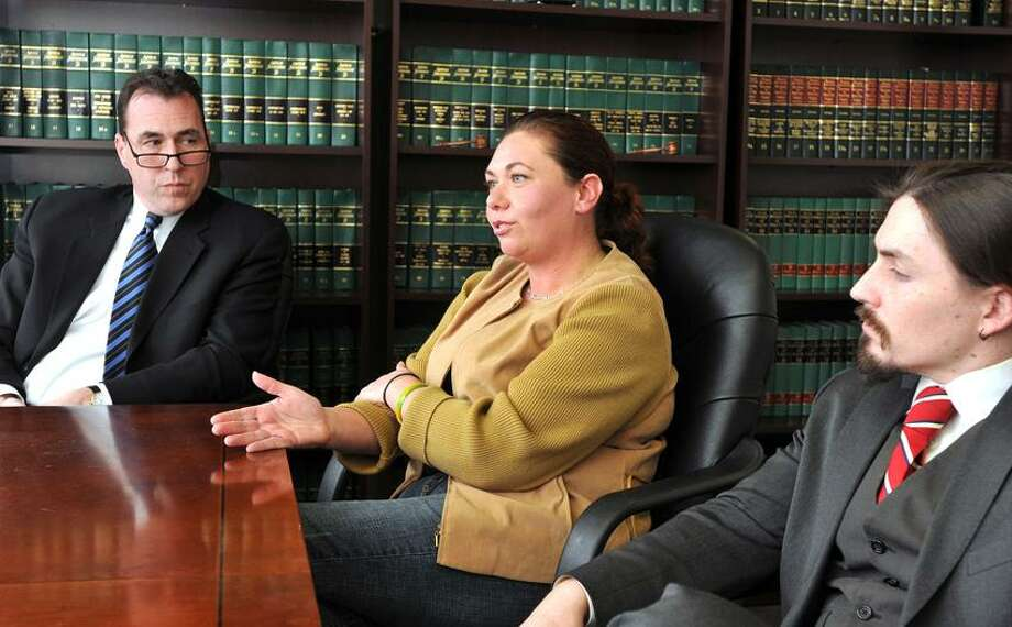 Erica Berg, former secretary to former East Haven Mayor April Capone, speaks about her lawsuit against the town of East Haven during an interview. She is flanked by her attorneys Glenn Conway, left, and Kevin Smith.  Peter Casolino/Register