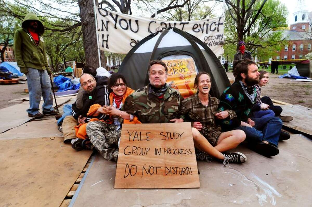 Occupiers share a lighter moment before bracing themselves for arrest. New Haven police broke up Occupy New Haven's camp on the Green. Thirteen people were arrested. Melanie Stengel/Register