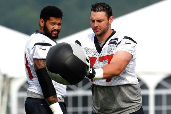 Houston Texans tackle David Quessenberry (77) knocks down a medicine ball during training camp at the Greenbrier on Thursday, July 27, 2017, in White Sulphur Springs, W.Va.