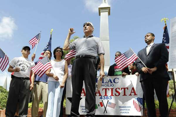 Mario Salas of the San Antonio Coalition of Human and Civil Rights (center), County Commissioner Tommy Calvert (right) and others gather for a press conference to demand the Confederate monument at Travis Park be removed. A reader says the effort represents political correctness run amok.