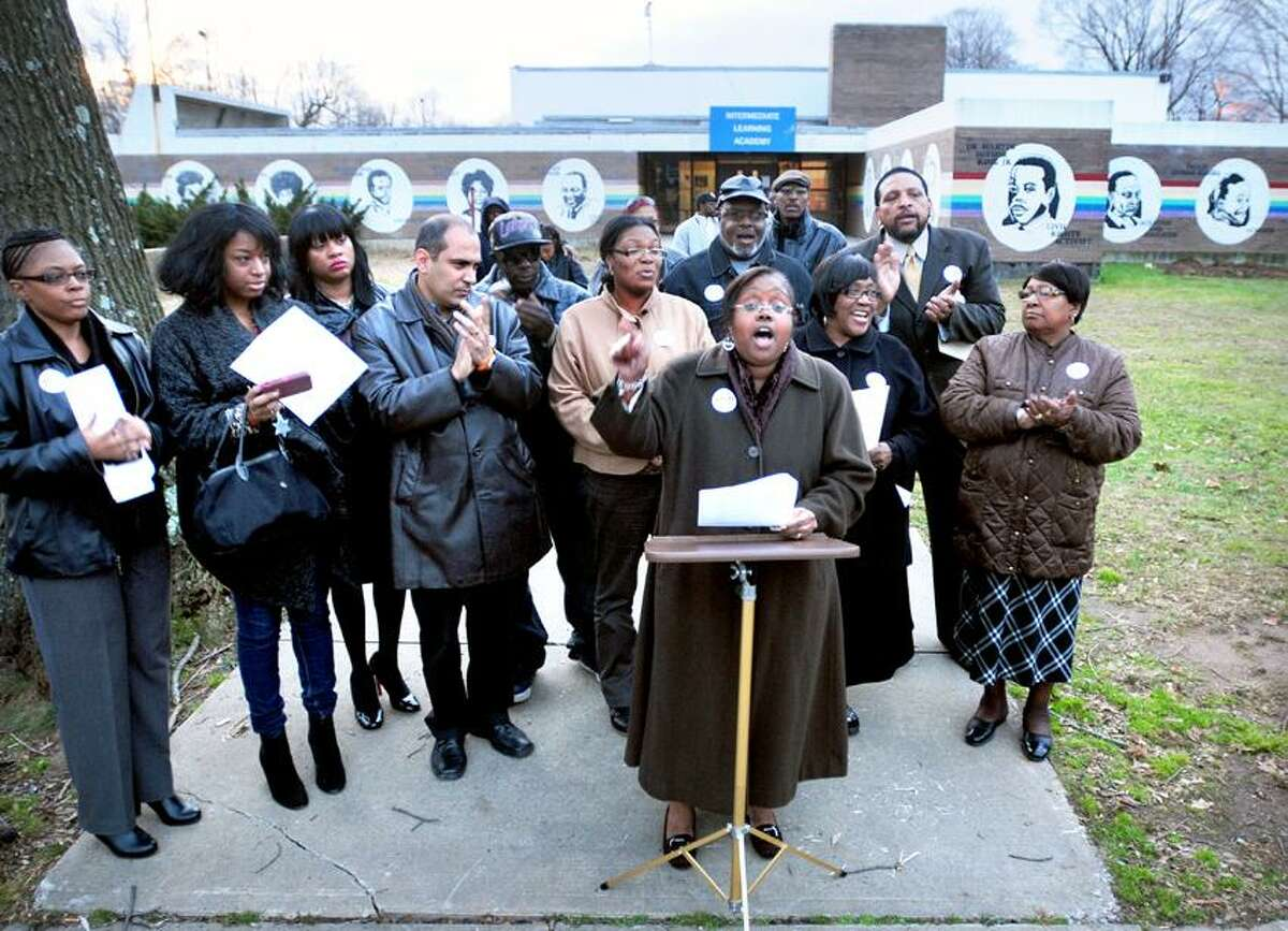Ward 20 Alderwoman Delphine Clyburn (center) surrounded by supporters speaks out in favor of the planned Achievement First school at the former Martin Luther King School in the background on Dixwell Ave. in New Haven. Photo by Arnold Gold/New Haven Register