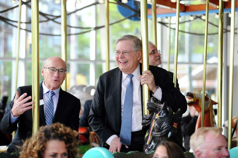 Stamford mayor David Martin, center, smiles while riding the Mill River Park carousel for the first time during the Mill River Park Collaborative's cocktail hour in Stamford, Conn. on Thursday, May 4, 2017. Also pictured is Arthur Selkowitz, left, the chairman of the Mill River Park Collaborative's Board of Directors. Photo: Michael Cummo / Hearst Connecticut Media / Stamford Advocate