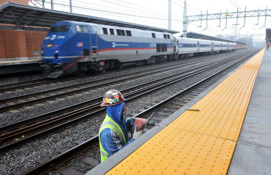 Alex Cordona of Acoustic Inc., works on the train platform at the new West Haven Train Station as a Metro North train speeds by.  Peter Casolino