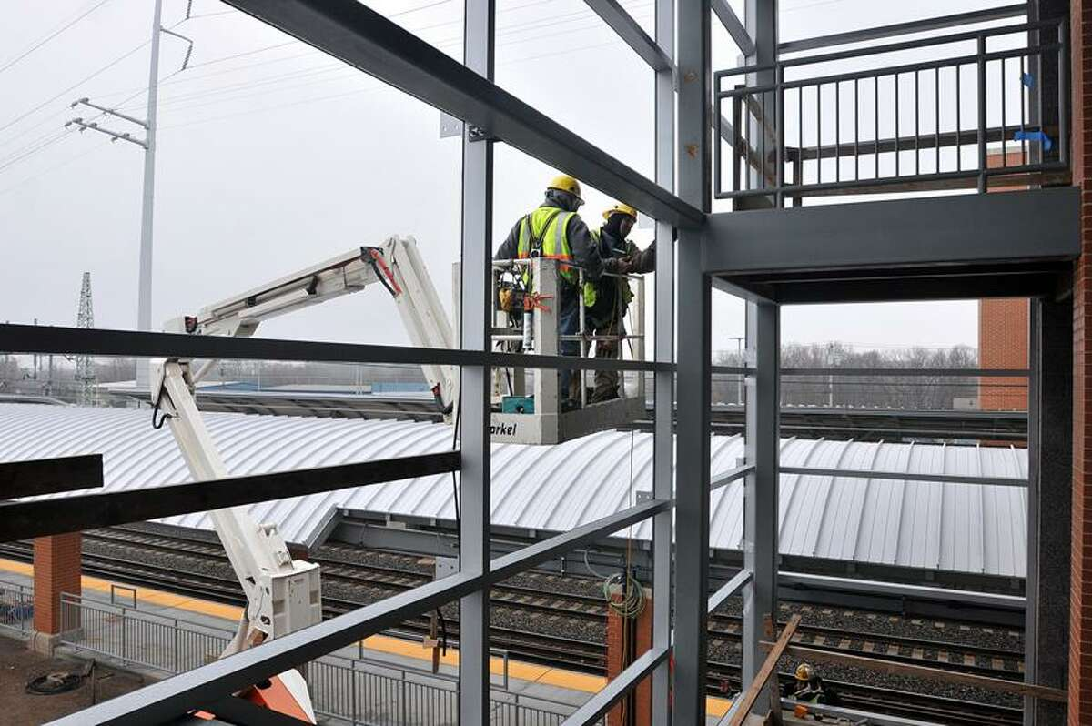 Glass installers work at the new West Haven Train Station. Peter Casolino