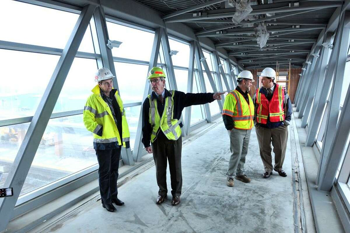 From left, Lynn Cichowski, assistant district engineer for DOT, Gene Colonese, rail administrator, DOT, George Cooper, resident engineer, STV Engineering firm, and Rich Jankovich, assistant rail administrator discuss the progress of the new West Haven Train Station from the glass walkway over the rails. Peter Casolino
