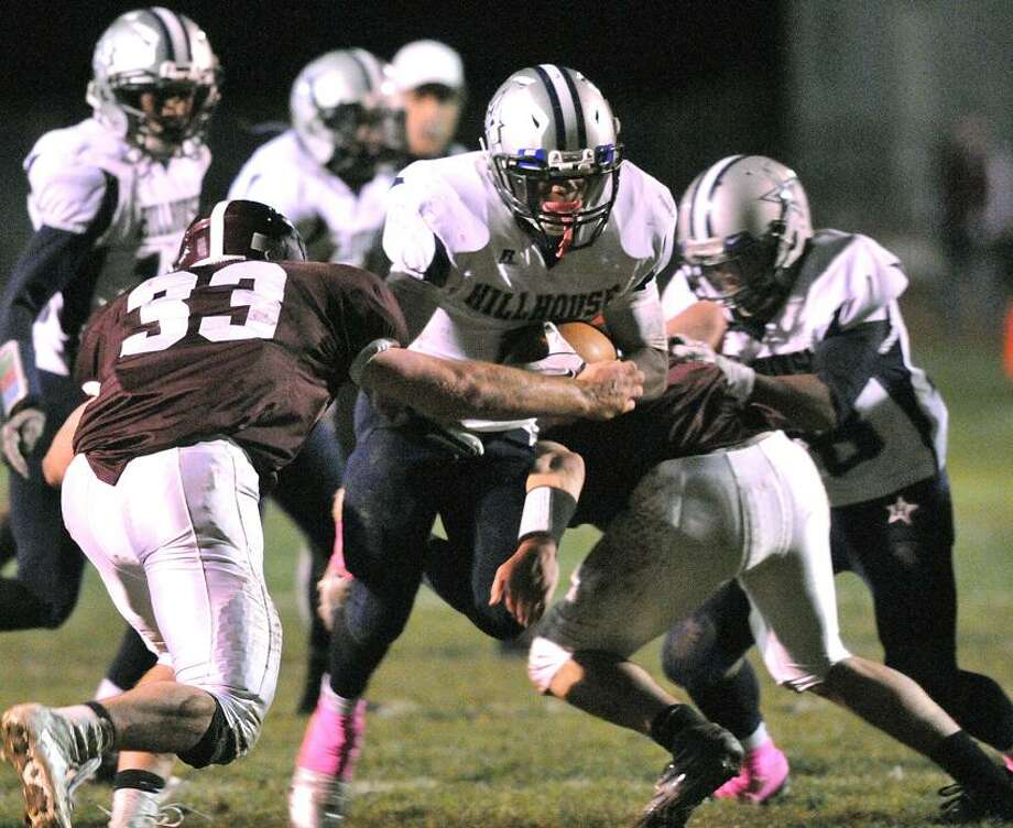 North Haven-- Hillhouse's Harold Cooper breaks through the North Haven line during the second quarter.  Making the tackle is Ethan Suraci (#33) left, and Connor McDonald. Photo by Peter Casolino/New Haven Register