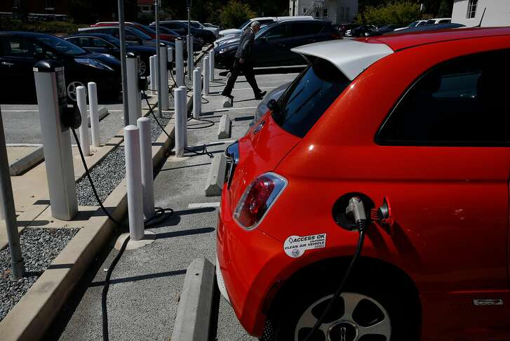 A person walks past electric car charging stations in a parking lot in the Presidio July 25, 2017 in San Francisco, Calif.