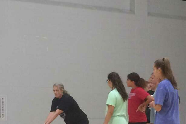 Coach Kelly Miser demonstrates a technique at the Kingwood Park Volleyball Camp