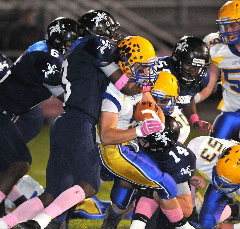 Ansonia-- The Ansonia defense swarms Seymour's Joseph Salemme during the second quarter. Making the tackle is Saiheed Sanders, left, and Joe Price, bottom (#14). Photo Peter Casolino/New Haven Register