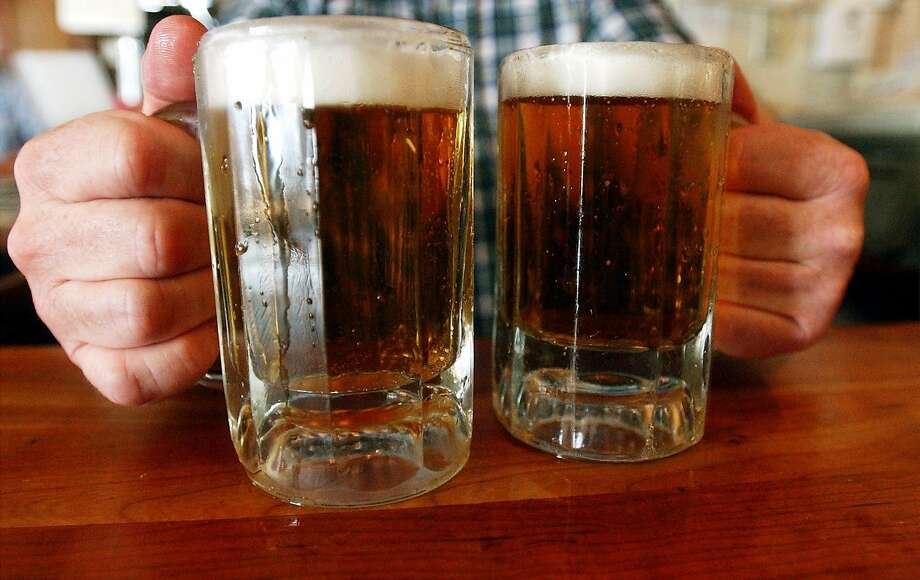 FILE - In this Tuesday, June 29, 2004 file photo, a bartender serves two mugs of beer at a tavern in Montpelier, Vt. Americans are drinking more than they used to, a troubling trend with potentially dire implications for the country's future health-care costs. Photo: Toby Talbot, AP