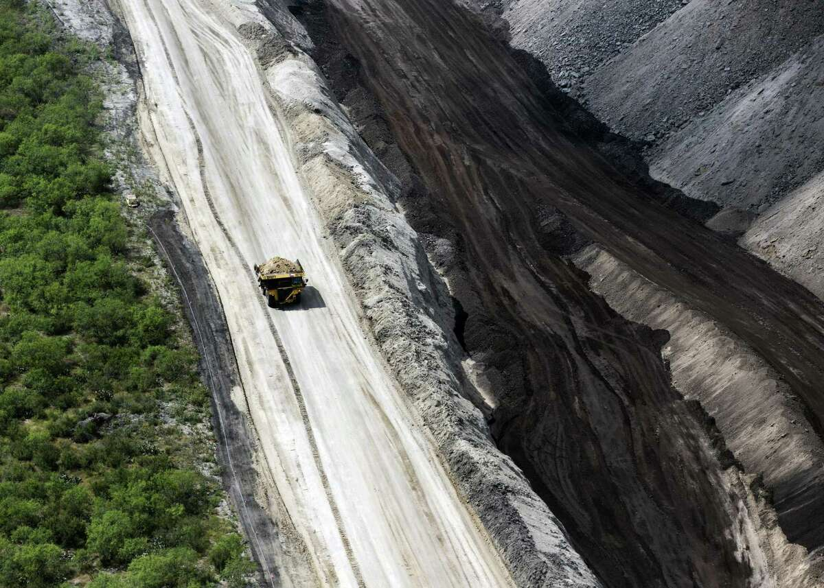 A large coal mine-style dump truck moves material at the San Miguel lignite coal mine near Campbellton, Texas in this Wednesday, May 17, 2017 aerial photo. The San Miguel Electric Cooperative's longtime lignite mine, which supplies the fuel for its nearby power plant, wants to expand its footprint in McMullen County.