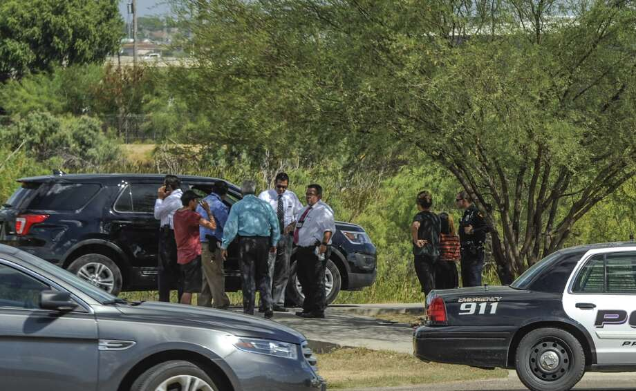 Investigators speak to people near the Haynes Recreation Center on Tuesday, July 27, 2017, where the body of a teen was discovered in the brush next to the walking trails. Photo: Danny Zaragoza, Laredo Morning Times