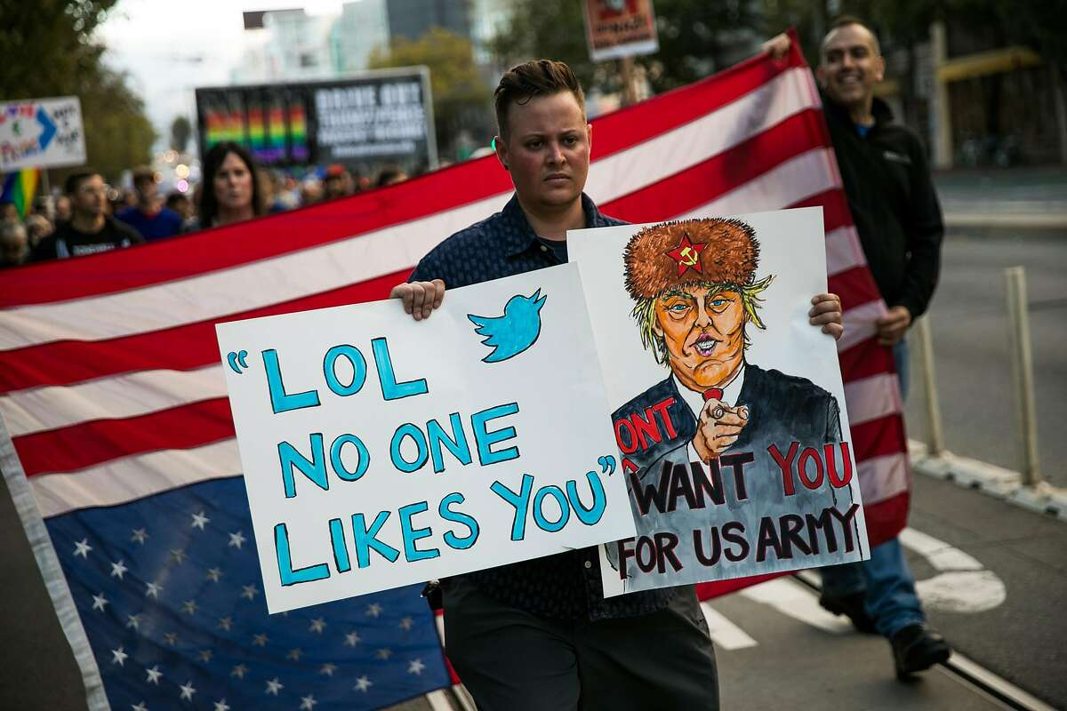 Max Repka holds up his signs as hundreds of people march down Market Street to protest President Trump's tweeted vow to ban transgender people from the military, on July 26, 2017 in San Francisco.
