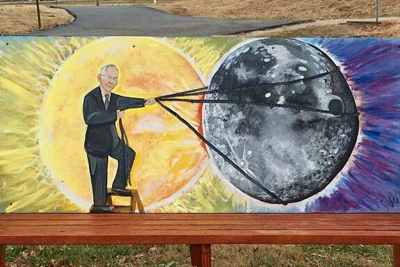 A bench outside the recreation department in Hopkinsville, Kentucky, depicts two town highlights: the coming solar eclipse, with Hopkinsville-born mystic Edgar Cayce lassoing the moon.