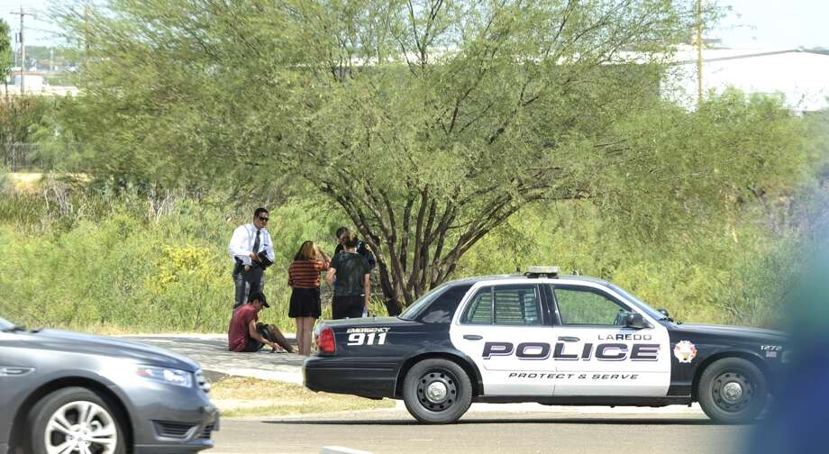 Investigators speak to people near the Haynes Recreation Center on Tuesday, July 27, 2017, where the body of Lesley Sanchez was discovered in the brush next to the walking trails. Photo: Danny Zargoza, Laredo Morning Times