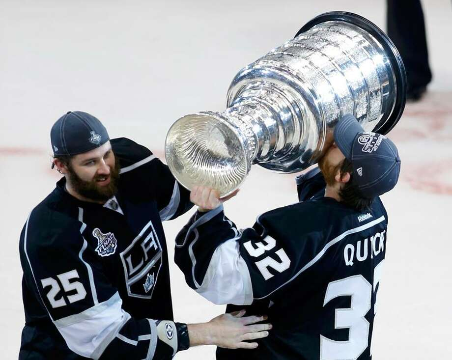 b5a5f6fe876 Los Angeles Kings goalie Jonathan Quick (R) kisses the Stanley Cup next to  teammate