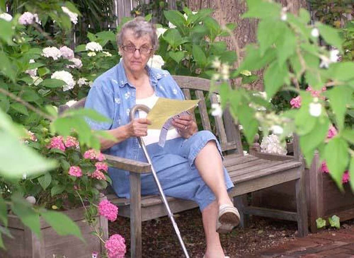 Janet Moore of Middletown sits one a bench during a tour of Juanie Flagg's gardens on her property on Laural Grove Road