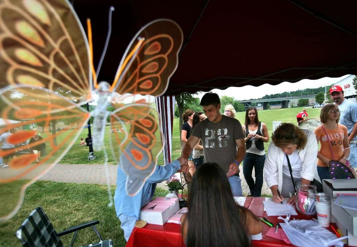 People make donations to the Shelton Butterfly Project at the foundation's booth at the Riverwalk in Shelton on Sunday, June 13, 2010.
