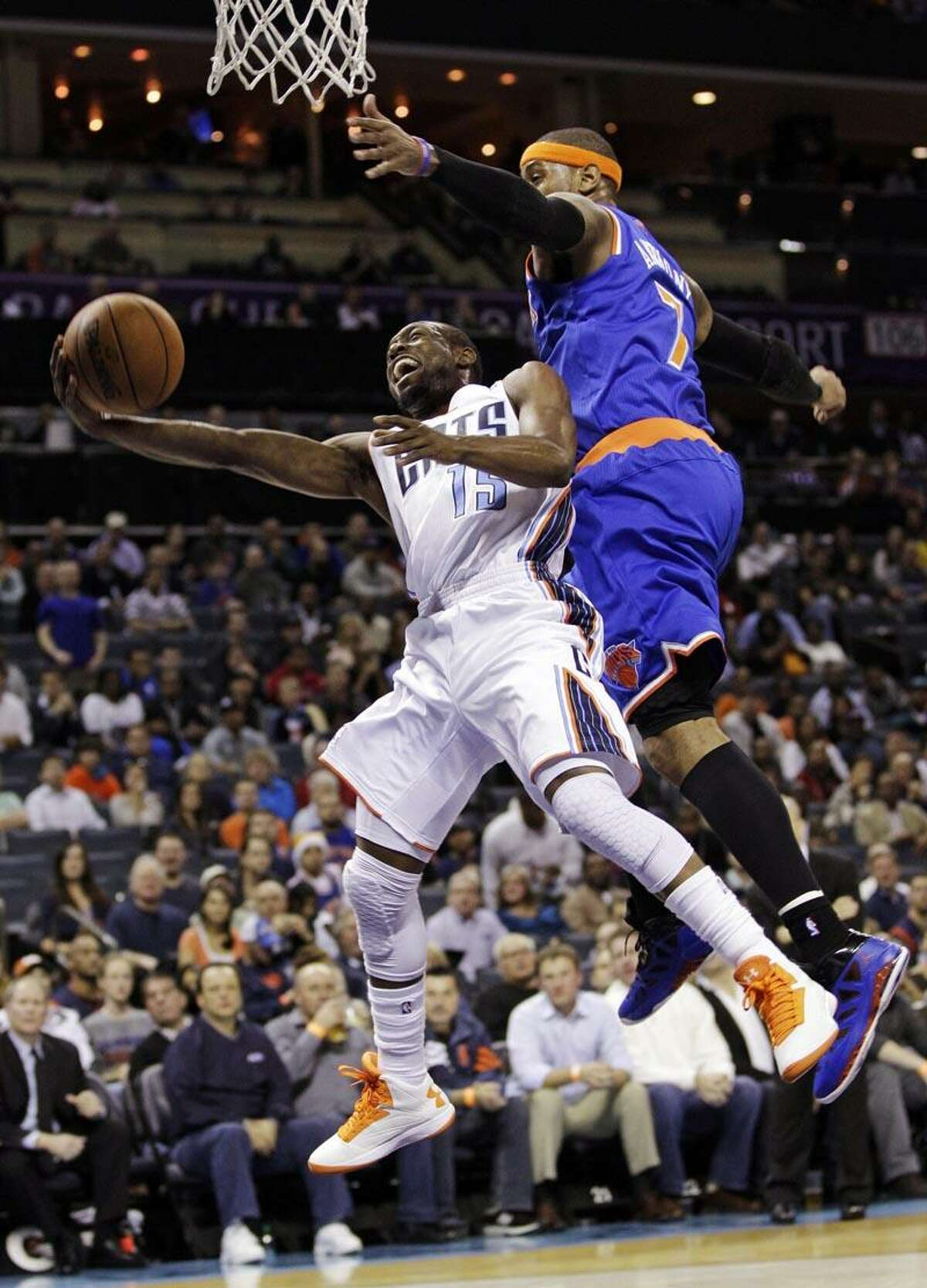 Charlotte Bobcats' Kemba Walker (15) is fouled as he drives past New York Knicks' Carmelo Anthony (7) during the first half of an NBA basketball game in Charlotte, N.C., Wednesday, Dec. 5, 2012. (AP Photo/Chuck Burton)