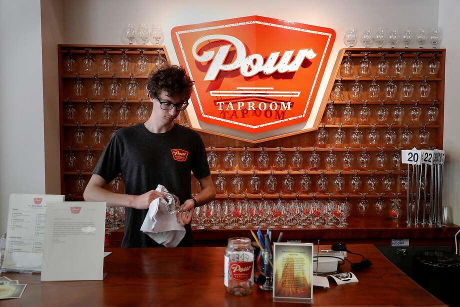 John Watson works the front desk and is also a server at pour-your-own Pour Taproom in Santa Cruz. Photo: Michael Macor, The Chronicle
