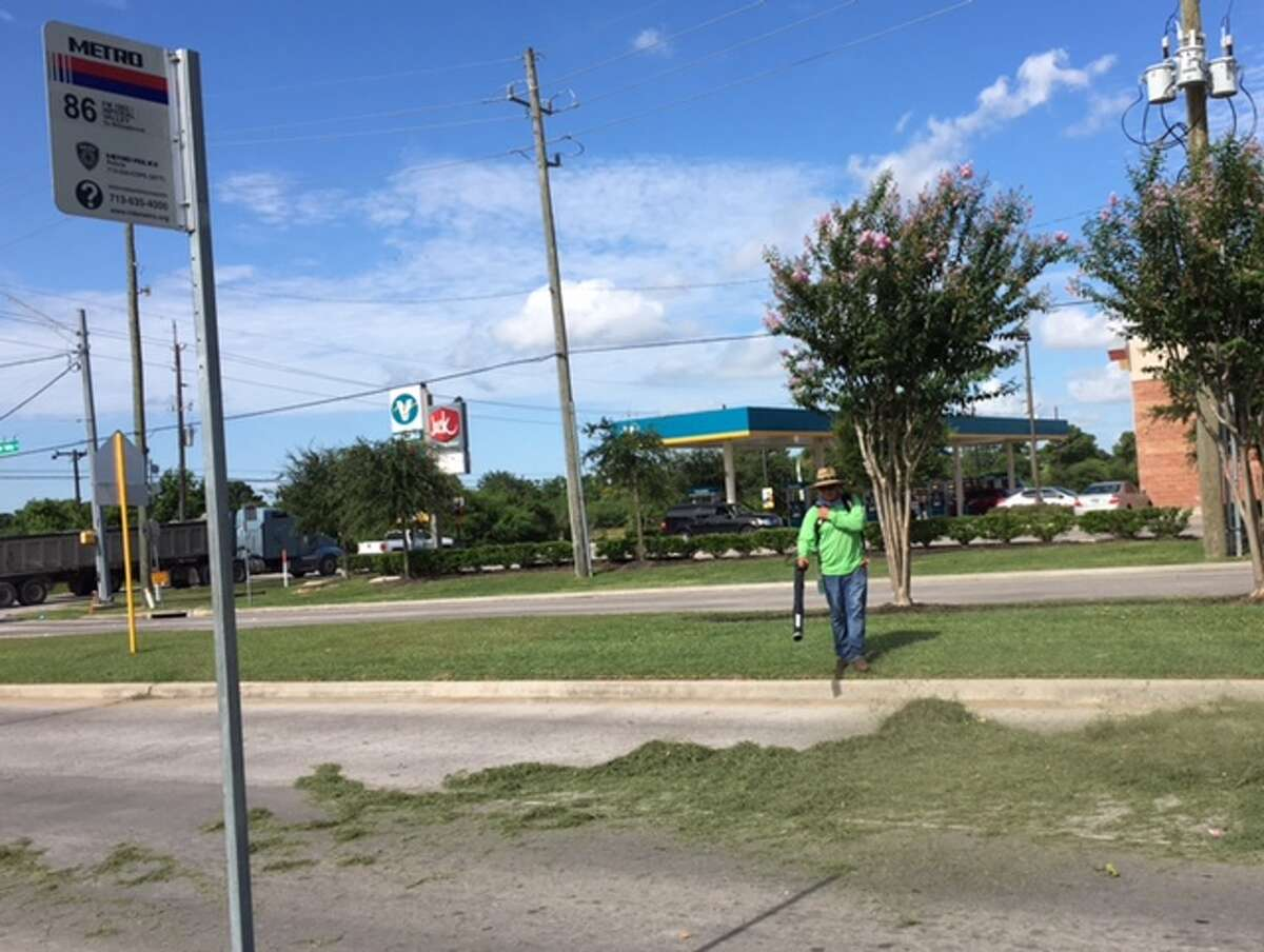 A landscaper works near a bus stop on the 86-FM 1960 route. Some stops have no benches or shade.