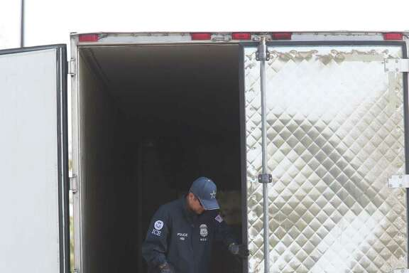 Law enforcement personnel survey the scene where nine immigrants died in a tractor-trailer at a Walmart in San Antonio.