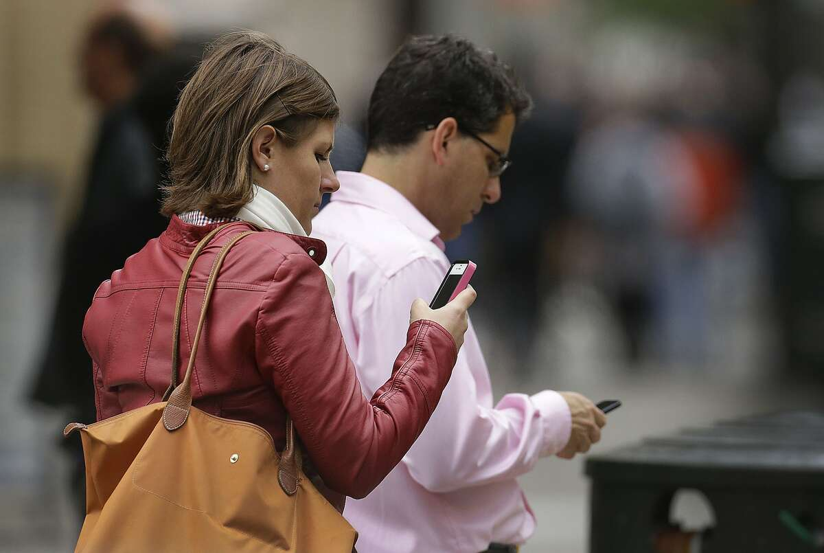 """FILE - In this June 5, 2013, file photo, people use cellphones in downtown San Francisco. San Francisco's top prosecutor said Monday, Nov. 18, 2013, that Samsung Electronics, the world's largest mobile phone manufacturer, has proposed making a """"kill switch"""" that would render stolen or lost phones inoperable a standard feature, but the nation's biggest carriers have rejected the idea. District Attorney George Gascon says AT&T, Verizon Wireless, US Cellular, Sprint and T-Mobile rebuffed Samsung's proposal to preload its phones with Absolute LoJack anti-theft software. (AP Photo/Ben Margot, File)"""