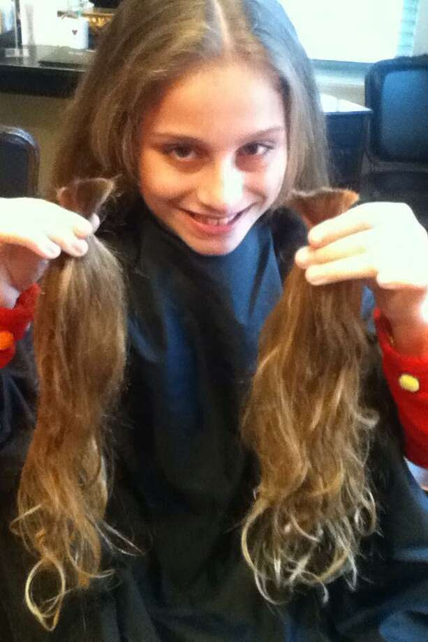 Elisa DiLegge of Litchfield shows the plaits of hair that will be donated to Locks of Love. Elisa is a 5th-grader at Litchfield Intermediate School. She had her hair cut at the Spa at Litchfield Hills in Litchfield last weekend.
