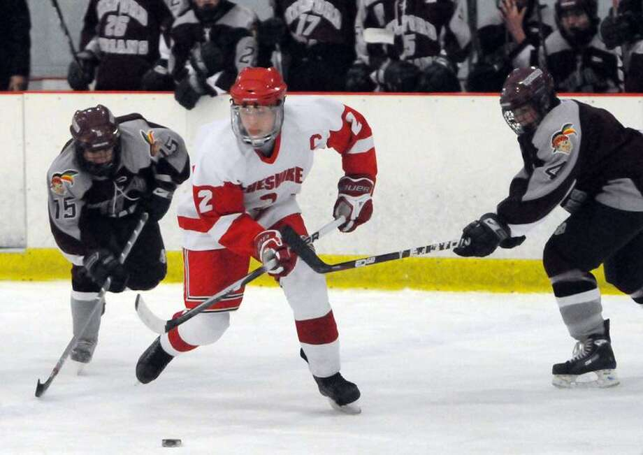 Cheshire's Spencer Hackett, center, moves the puck up the ice against Ricky Cyr, left, and Jonathan DePascale of Milford during first-period hockey action at the Northford Ice Pavilion.  Photo by Peter Hvizdak/ New Haven Register Photo: New Haven Register / ©Peter Hvizdak /  New Haven Register