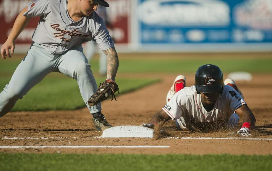 Loons right fielder Carlos Rincon slides back into first base as Bowling Green's Robbie Tenerowicz fails to tag him out during their game on Thursday, July 27, 2017 at Dow Diamond. Photo: (Katy Kildee/kkildee@mdn.net)