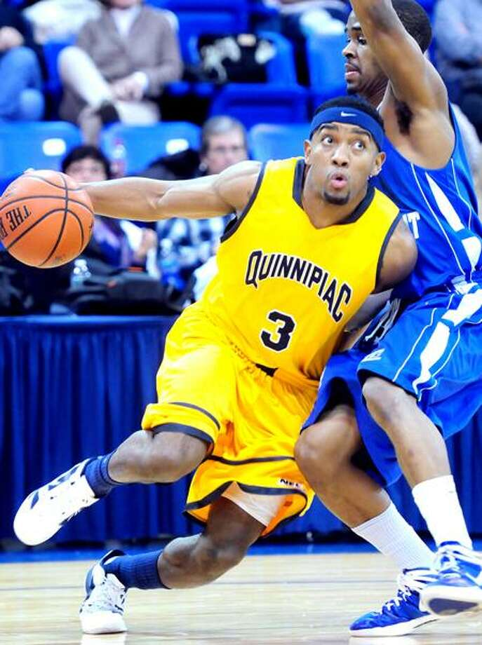 James Johnson (left) of Quinnipiac University drives past Kyle Vinales (right) of Central Connecticut State University in the first half at the TD Bank Sports Center in Hamden on 2/8/2012.Photo by Arnold Gold/New Haven Register   AG0438D