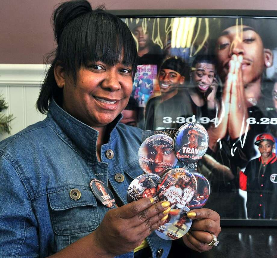 "Virginia Williams shows off some of the remembrance buttons she makes at her shop, TJ Custom Designz. Williams' son, Travis ""TJ"" Washington, was killed in a shooting last June.    Peter Casolino/New Haven Register"