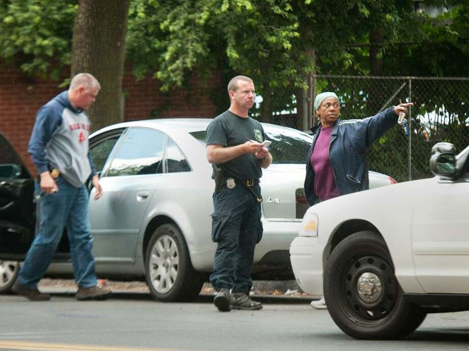 Audrey Richards stands behind her car and talks to police, after her son, Joseph Harrison, was handcuffed and placed in a police cruiser. Harrison says he was a passenger in Richard's car when they were pulled over. He says police pointed  a gun at his mother, and when he protested he was taken into custody. Harrison was later released at the scene but says he was issued a ticket for creating a disturbance. A shooting had happened in the area and Richard's car possibly fit the description of an involved vehicle. Melanie Stengel/Register