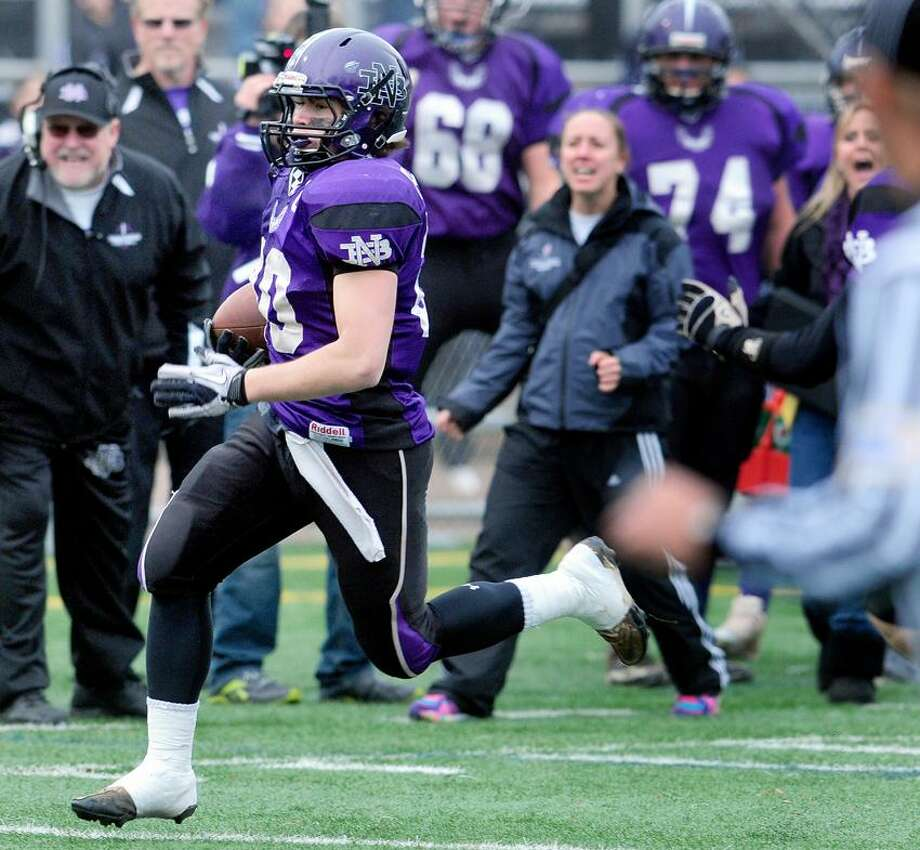 Dale Hausman (left) of North Branford runs for long yardage against Woodland in the first quarter of the Class S semifinal in Meriden on 12/2/2012.Photo by Arnold Gold/New Haven Register
