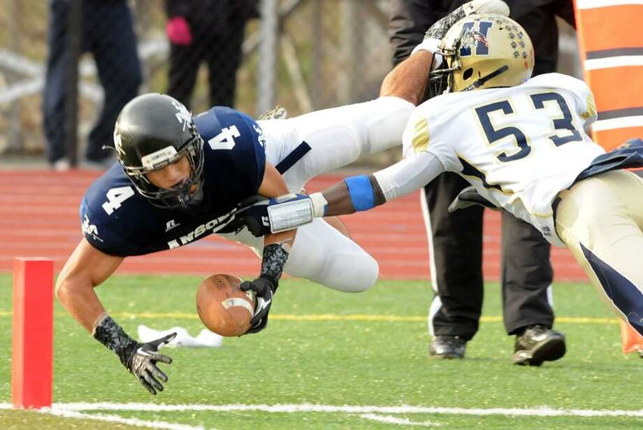 Ansonia's Andrew Matos is tackled by Hyde's Kahlil Morant one play before the team's last touchdown in the Class S semifinals won by third-ranked Ansonia. Mara Lavitt/New Haven Register.