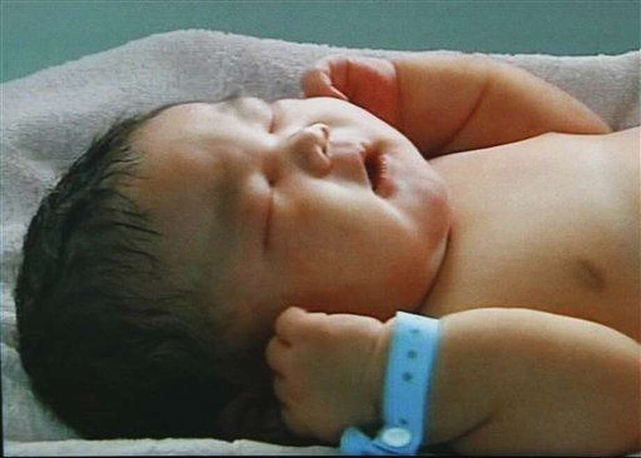 In this image made on Feb. 4 from CCTV television, a 15-pound baby named Chun Chun, sleeps at Xinxiang Maternity Hospital, in Xinxiang city, Henan province, China. Associated Press Photo: ASSOCIATED PRESS / AP2012