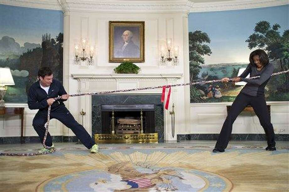 """In this image released by The White House, first lady Michelle Obama participates in a tug of war with television host Jimmy Fallon in the Blue Room of the White House during a taping of """"Late Night with Jimmy Fallon,"""" for the second anniversary of the """"Let's Move!"""" initiative on Jan 25, 2012, at the White House in Washington. The segment is scheduled to air on Tuesday. Associated Press Photo: ASSOCIATED PRESS / AP2012"""
